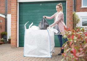 Home waste being transferred into a skip bag