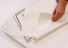 Wrapping a framed picture with white news wrapping paper